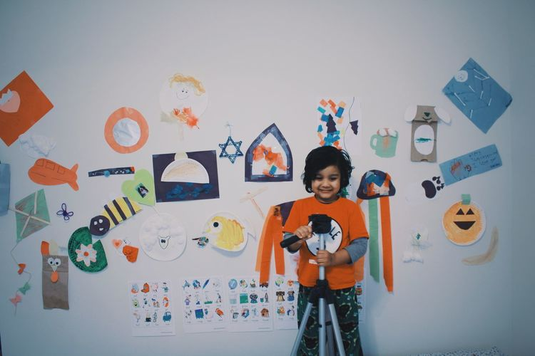 Cute Girl Standing With Tripod Against Wall Art