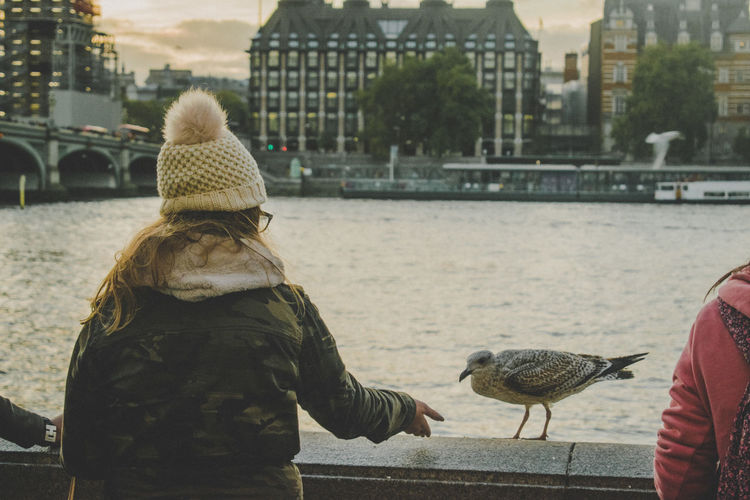 Architecture Bird Building Exterior Built Structure City Day Focus On Foreground Friendship Large Group Of Animals Leisure Activity Lifestyles Mammal Men Nature Outdoors Perching Real People Rear View River Sitting Togetherness Two People Warm Clothing Water Connected By Travel