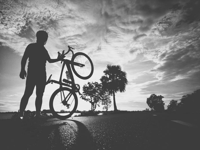 Silhouette of man with bicycle