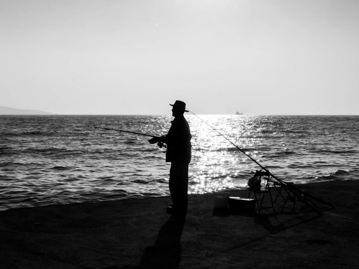 Silhouette man fishing in sea against clear sky