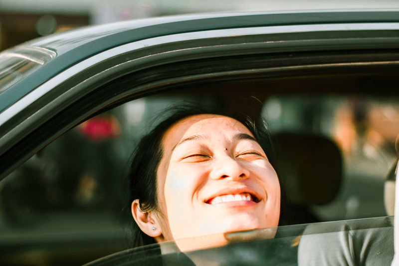 Close-Up Of Smiling Young Woman In Car