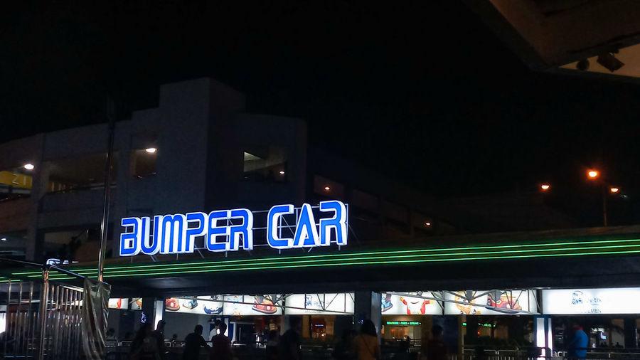 Illuminated sign on street in city at night