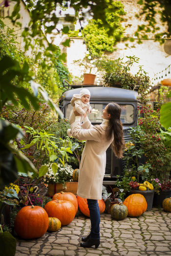 Woman playing with daughter while standing by pumpkins against trees