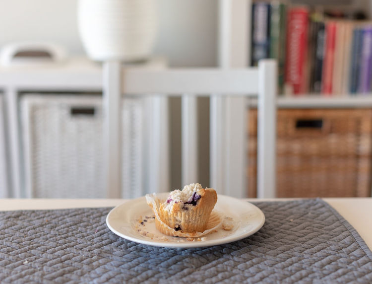 Half finished muffin Baked Breakfast Close-up Crockery Day Dessert Domestic Room Focus On Foreground Food Food And Drink Freshness Indoors  Indulgence No People Place Mat Plate Ready-to-eat Still Life Sweet Sweet Food Table Temptation
