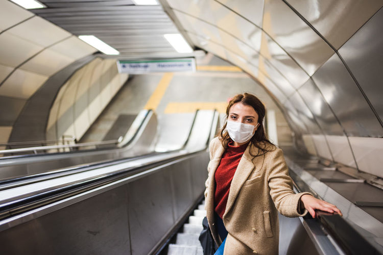 Portrait of woman standing on escalator at subway station