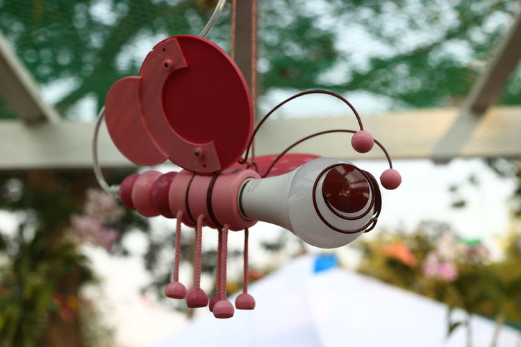 Low angle view of red bell hanging on tree