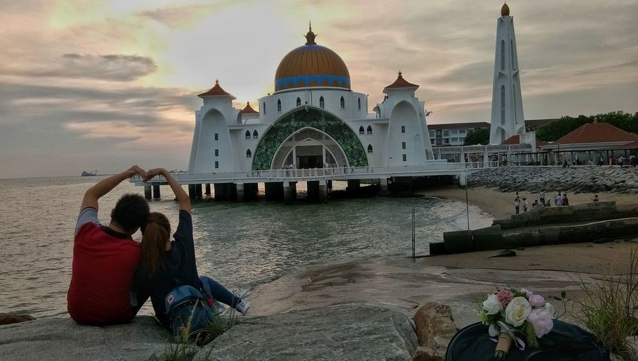 Loving couple in love sign facing strait mosque with sunset background Couple In Love Love Sign Facing Floating On Water White Mosque Dronephotography Tourist Attraction  Tourist Destination Touristic Destination Water Dome Religion Sunset Sky Architecture Historic Place Of Worship Pilgrimage Mosque Islam Spirituality Building Tower