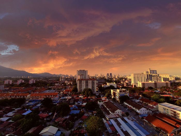 High angle view of city buildings against sky during sunset