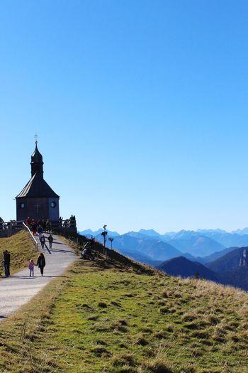 People walking towards church at bavarian alps