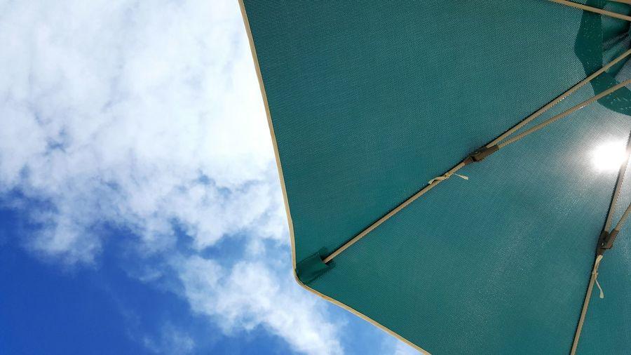 Directly below shot of beach umbrella against cloudy sky