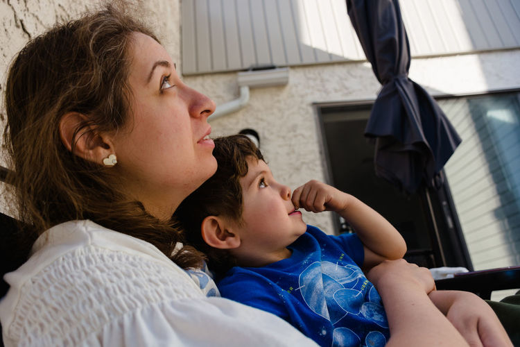 Mother and son looking up while sitting outdoors