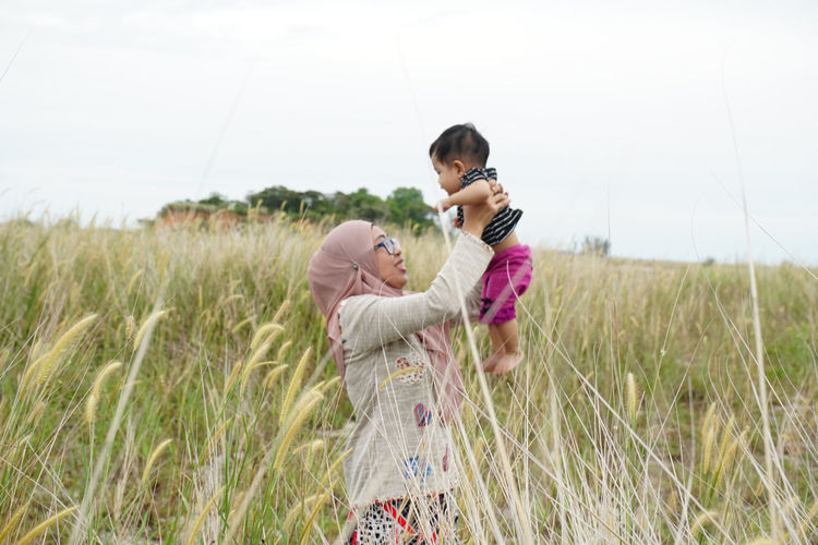 Side view of mother playing with daughter on field