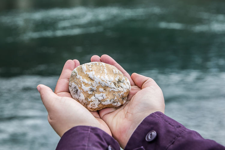Close-up of hand holding stone over water
