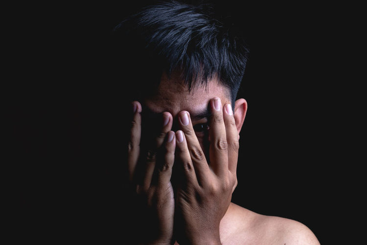 Close-up of hand covering face against black background