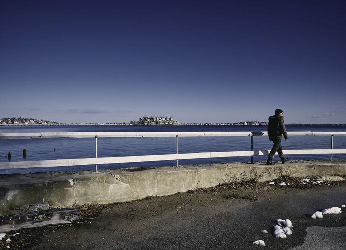 Man Walking By Sea In City Against Sky