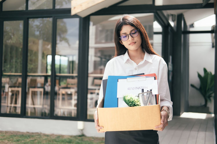 Unemployed woman carrying box while standing against office