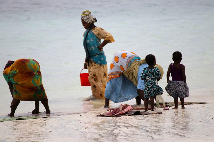 Women working by girls at beach