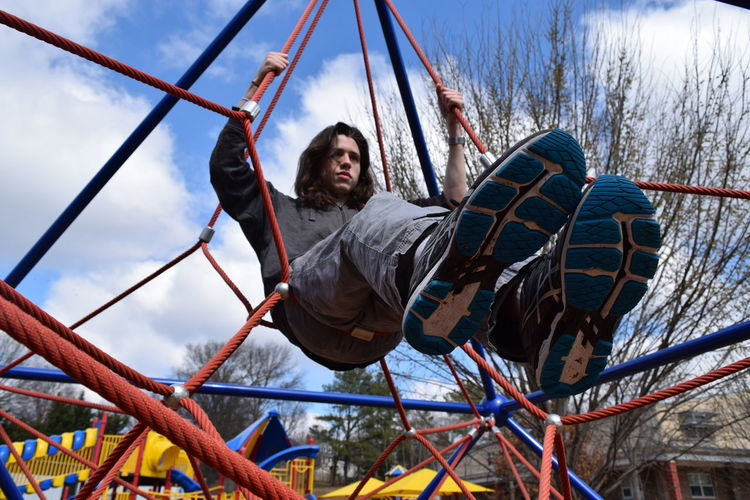 Low angle view of man sitting on play equipment at park