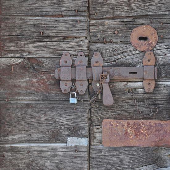 Rusty padlocks on wooden door