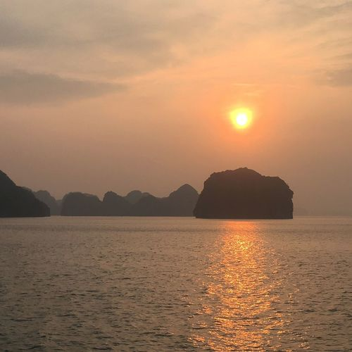 Ha Long Bay Cruise Ha Long Bay Vietnam Sunset Beauty In Nature Scenics Sea Nature Tranquility Tranquil Scene Sun Sky Water Orange Color Mountain No People Waterfront Reflection Outdoors Day