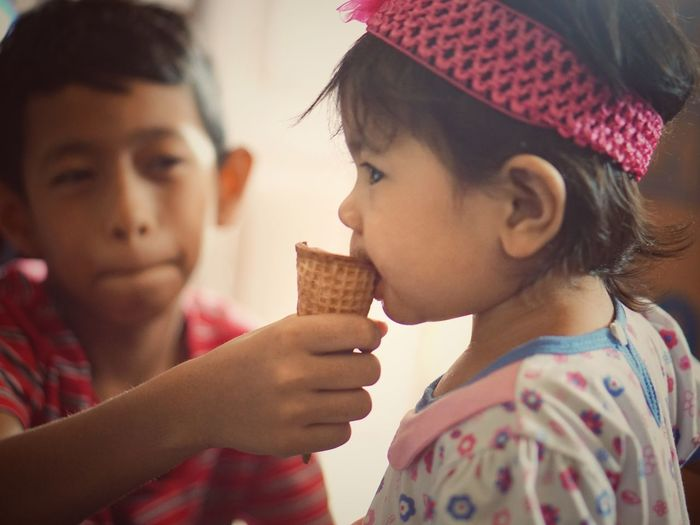 Boy feeding ice ream cone sister at home