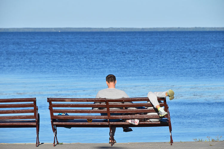 Couple Sitting On Bench At Shore Against Sea