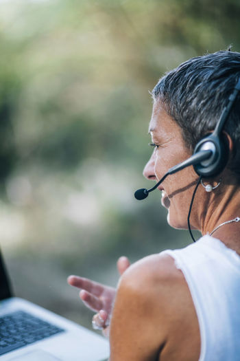 Remote work. positive middle-aged woman working remotely, wearing a headset, talking