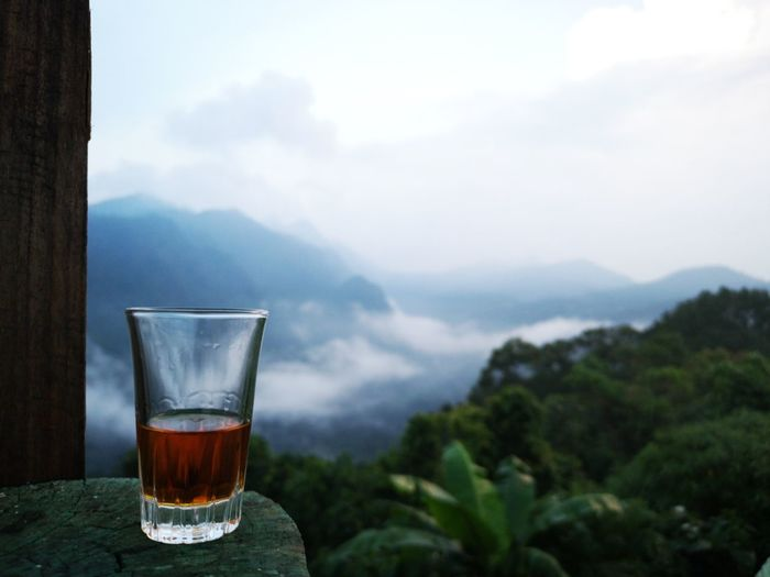 Whiskey glass on table against mountains