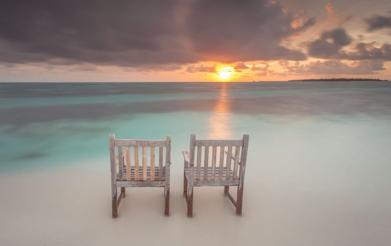 Chairs on beach against cloudy sky during sunset