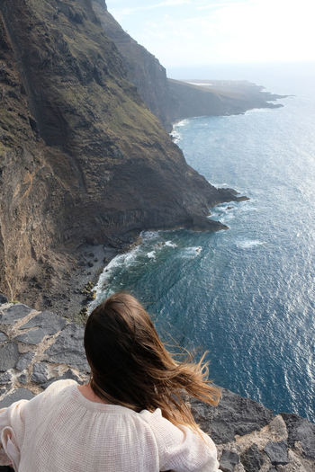 Rear view of woman looking at sea while standing on mountain