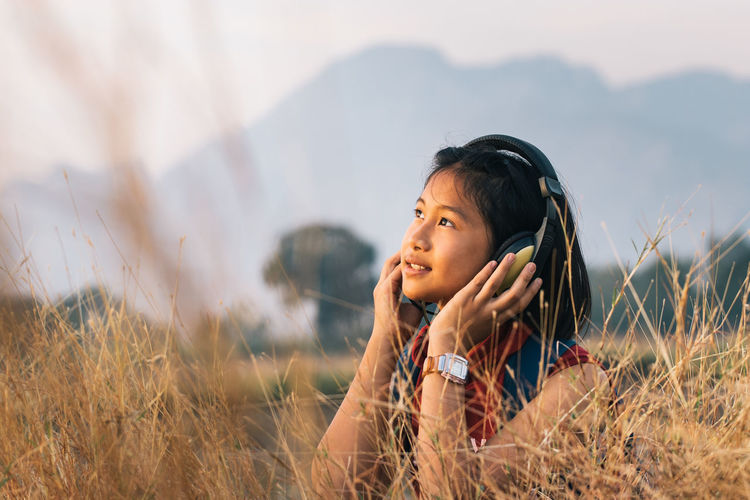 Mountain Freedom Relaxing Listening To Music Hairstyle Innocence Outdoors Contemplation Headshot Looking Women Casual Clothing Lifestyles Day Plant Selective Focus Field Grass Portrait Childhood Land Leisure Activity Nature Child Landscape