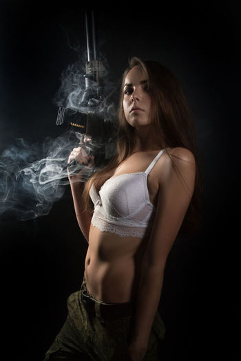 Activity Adult Beautiful Woman Beauty Black Background Dark Hair Hairstyle Holding Indoors  Long Hair One Person Portrait Semi-dress Smoke - Physical Structure Smoking Issues Studio Shot Women Young Adult Young Women