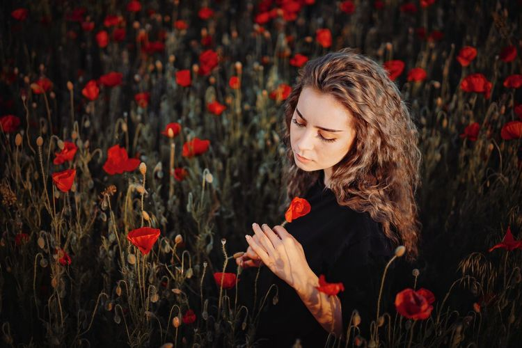 Young woman standing in red poppy flowering plants