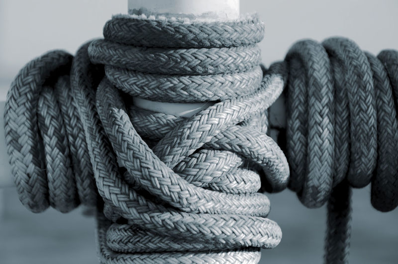 Close-up of rope coiled around pole