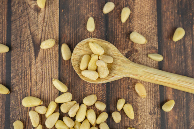 Many pine nuts with wooden spoon and wooden background, top view Pine Nuts Wooden Nut Top Food Healthy Organic Ingredient Natural Background Cooking Seed Nature Spoon Fresh Nutrition Vegetarian Cuisine Cedar Raw Closeup View Wood Diet Snack Dietary Season  Dry Rustic Seeds Health Pinus Pinea Macro Group Traditional Detail Close Still