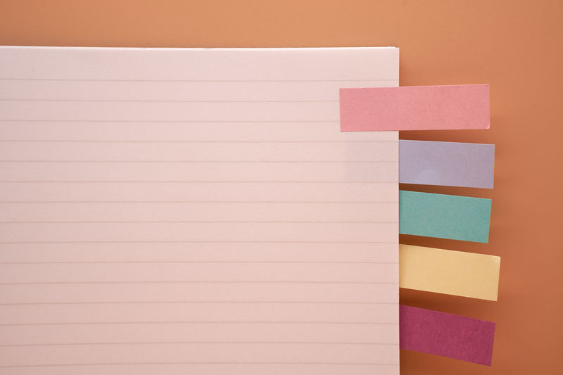 Directly above of diary with adhesive notes on brown background