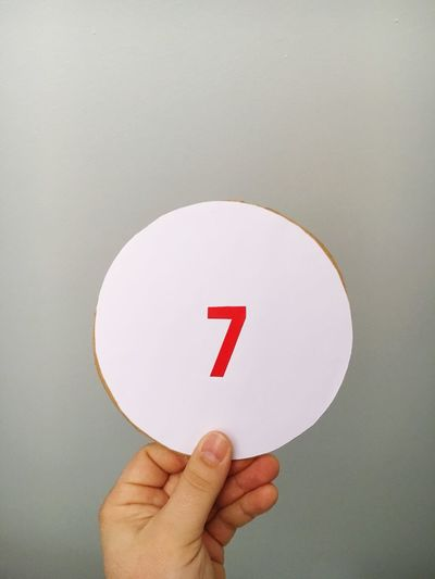 Cropped hand of person holding number on cardboard against gray background