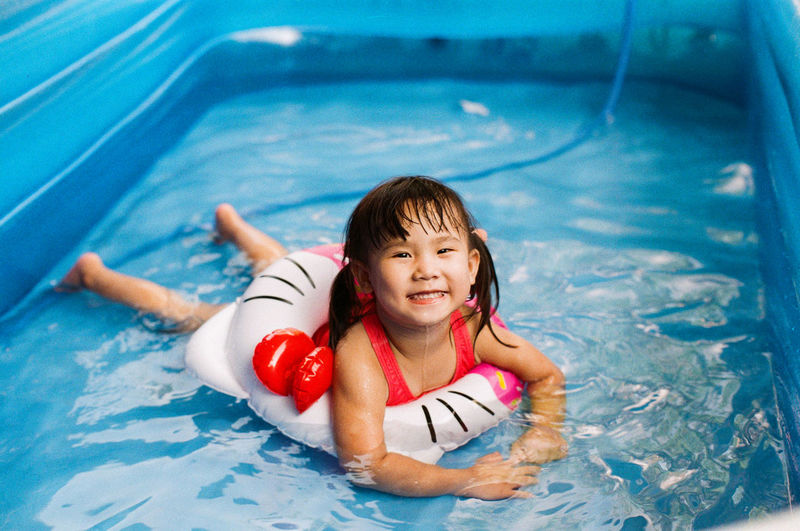 Asian little girl swimming in the pool. Pool Swimming Pool Child Childhood Water One Person Swimming Smiling Leisure Activity High Angle View Portrait Front View Nature Happiness Full Length Innocence Outdoors Floating On Water Kid Girl Female Swimming Offspring Nature Swimwear Happiness Looking At Camera Swimming Happiness Looking At Camera