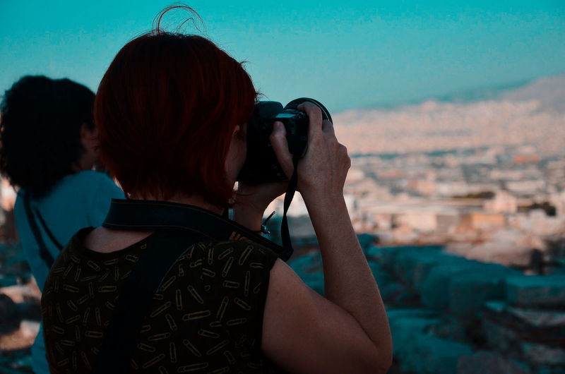Rear view of woman photographing with cityscape against sky