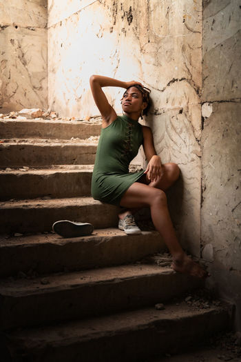 Full length of young woman sitting on staircase against wall