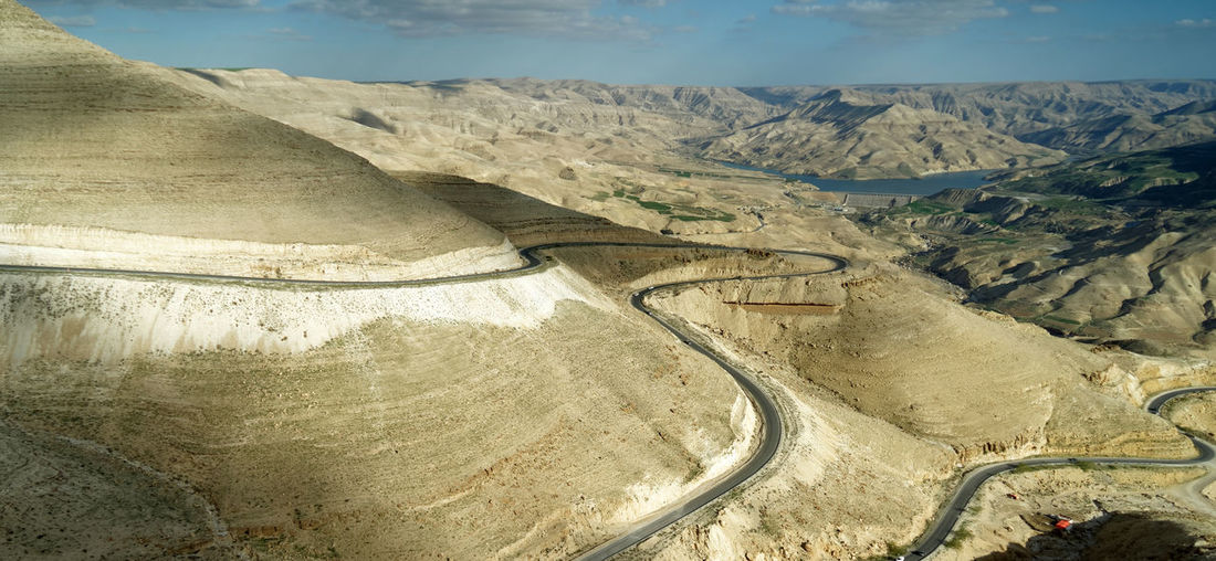 Panoramic view of the King Highway ascending the road north of the Wadi Mujib reservoir in Jordan. Ascending King Kings Highway Panoramic Road View Beauty In Nature Curve Day High Angle View Landscape Mountain Mountain Road Nature No People Non-urban Scene Outdoors Physical Geography Road Scenics Sky Tranquil Scene Tranquility Transportation Winding Road