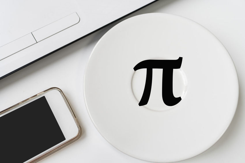 Happy Pi Day, written in black pen on white. On the desk a laptop, a cup, a hand holds the phone. Close-up Communication Day Indoors  No People Pi Day