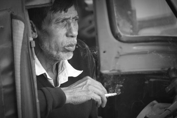 Man smoking while sitting jinrikisha