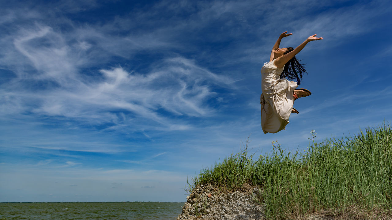 Full Length Of Woman Jumping On Field By Sea Against Sky