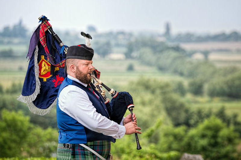 Bagpiper plays overlooking countryside Bagpiper Bagpipes Countryside Culture Flag Focus On Foreground Highlands Iconic Landscape Lifestyles Man Music Outdoors Rural Scene Scotland Scottish Tartan Tourism Tradition Traditional Traditional Culture Travel Travel Destinations Travel Photography Uk