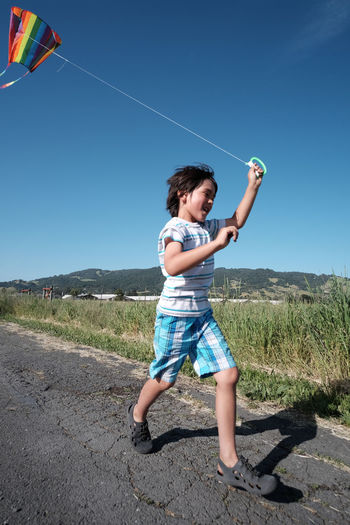 Cheerful Boy Holding Kite Running On Road By Grass Against Clear Sky