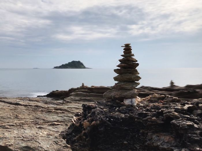 Stack of rocks by sea against sky
