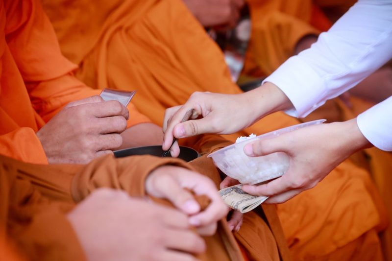 Cropped hands of person performing rituals with monks