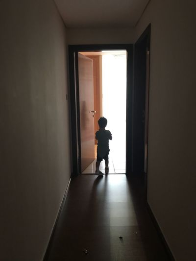 Rear view of silhouette boy standing on floor at home