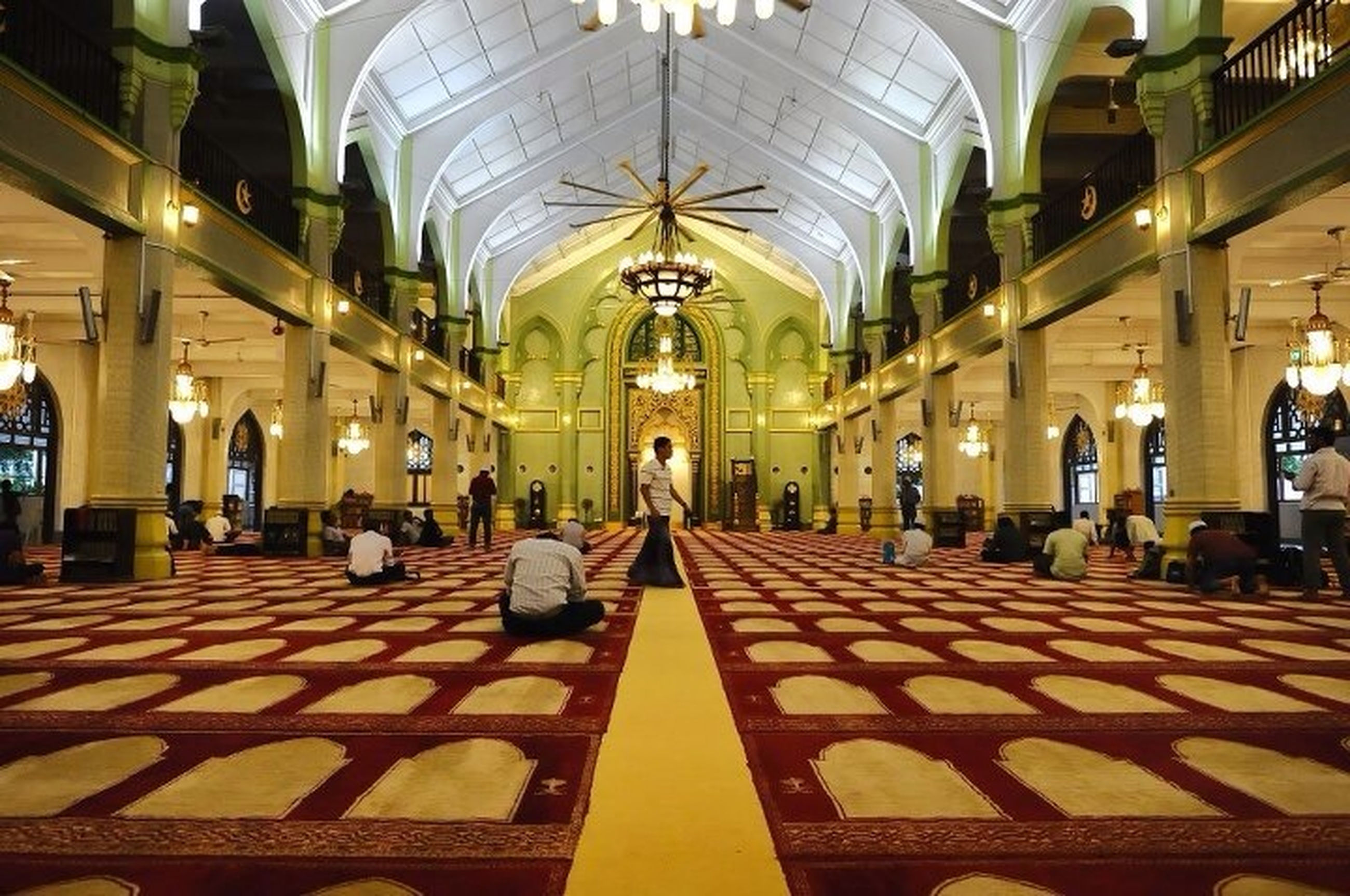 indoors, architecture, ceiling, person, large group of people, men, built structure, architectural column, arch, lifestyles, illuminated, corridor, travel, flooring, place of worship, railroad station, travel destinations, religion, leisure activity
